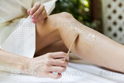Woman getting legs waxed at a spa