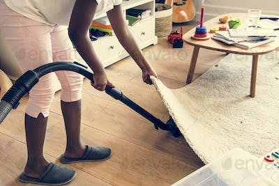Young teen girl vacuuming up the house