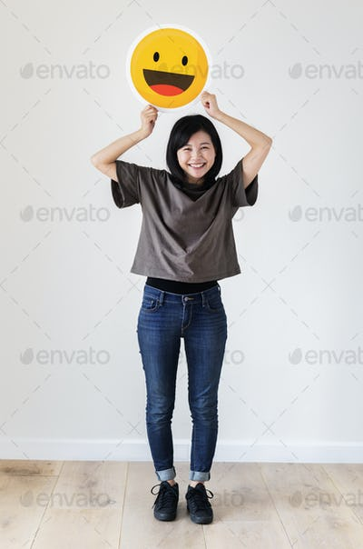 Happy Asian woman holding a smiley emoticon face