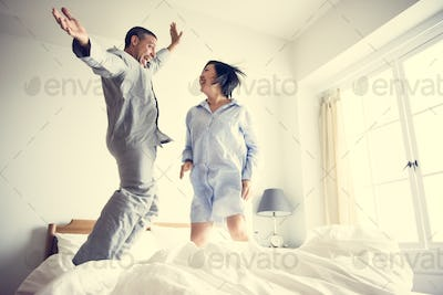 A couple jumping on the bed
