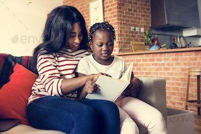 African mother helping her daughter in doing her homework