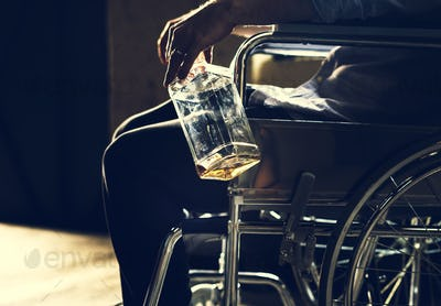 Alcoholic man sitting in a wheelchair