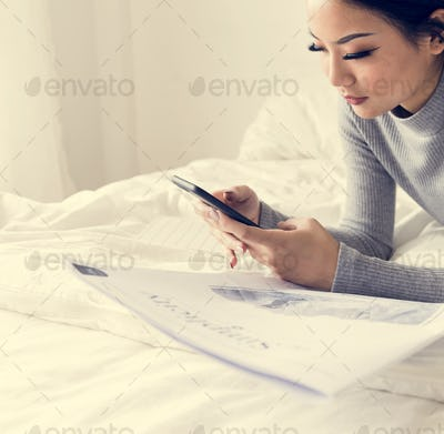 Asian woman lying on bed using mobile phone