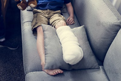 Kid with injured leg is sitting on the couch