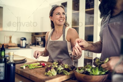 A couple is cooking in the kitchen together