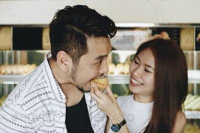 Asian girl feeding her boyfriend