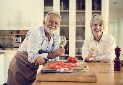 Senior couple enjoying white wine in the kitchen