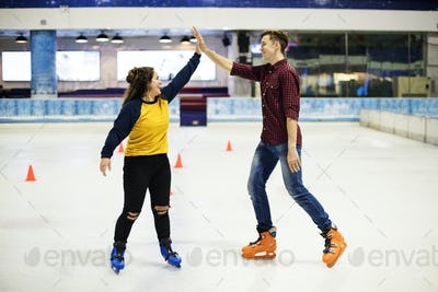 Friends giving each other a high five a they are ice skating on the ice rink
