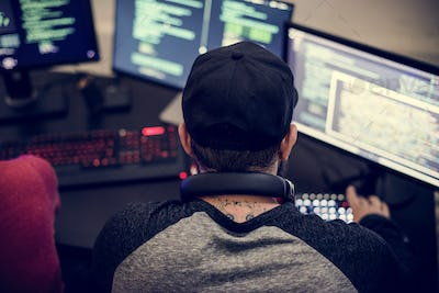 Caucasian tattooed man working on coding