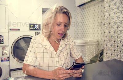 Caucasian woman waiting at the self service laundromat