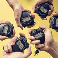 Closeup of hands holding stop watches with yellow background