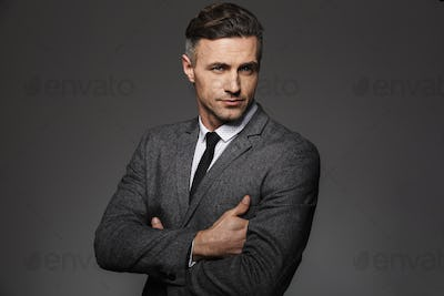 Portrait of masculine man wearing business suit posing on camera