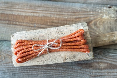 Smoked sausages on the wooden background