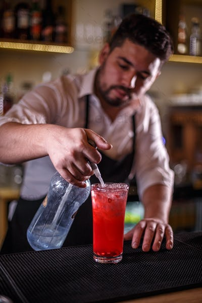 Bartender finishes preparing a cocktail