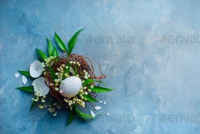 Floral Easter decoration concept with white eggs in a nest, green leaves and spring gypsophila