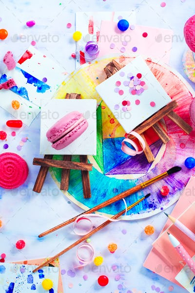 Tiny easels with confetti, pink macarons, candies, brushes and watercolor color wheel. Sweettooth