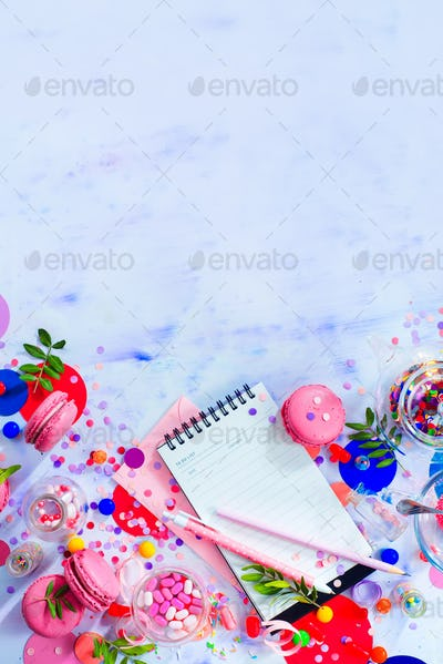 Planning a party concept with confetti, pink macarons, candies and an open notepad with blank pages