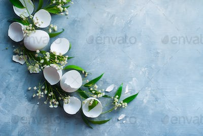 Header with raw eggs, decorative green leaves and spring flowers. Modern Easter concept with copy