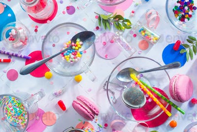 Sprinkles, confetti, candies, macaroons and birthday candles on a white background. Glass