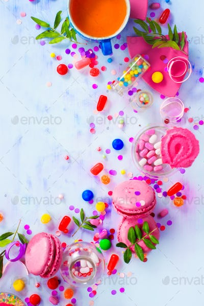 Pink macarons, candies, confetti and sprinkles in a creative party vignette with copy space