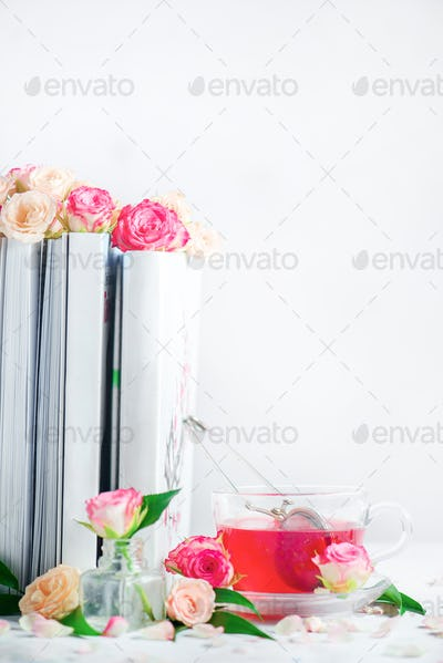 Bookshelf with white books, roses and a cup of herbal tea. Romantic leisure and reading concept on a