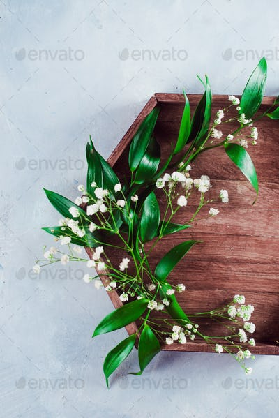Hexagonal wooden tray with green leaves and tiny white flowers. Spring flat lay on a concrete