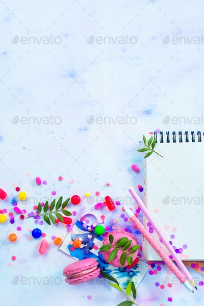 Blank pages notepad with sweets, candies, macarons and confetti on a light wooden background with