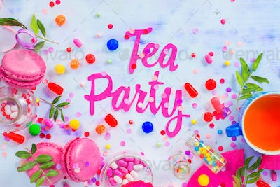 Tea party concept in pink tones with paper text, candies, sweets, confetti, macarons. Colorful