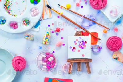 Tiny easel with confetti, pink macarons, candies, brushes and watercolor color wheel. Sweettooth