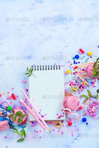 Open notepad with blank pages in an organizing a party concept with confetti, pink macarons, candies