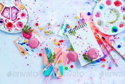 Sweettooth artist tools creative party concept. Pink macarons in a colorful party activity concept