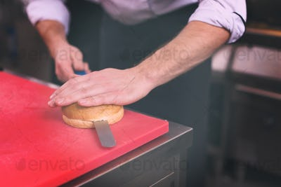 chef hands cutting rolls for burger
