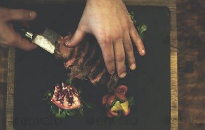top view of Chef hands serving beef steak