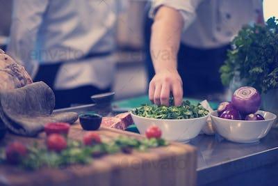 chef hand serving vegetable salad