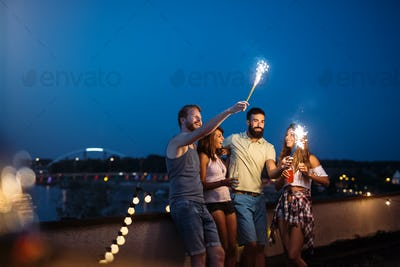 Friends enjoying a rooftop party and dancing with sparklers