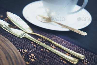 Detail of golden cutlery and a cup laid on a table