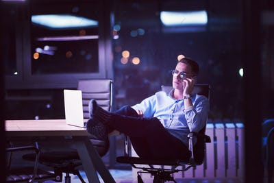 businessman using mobile phone in dark office