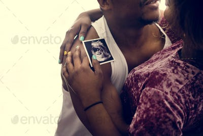 Black couple with baby ultrasound scan photo