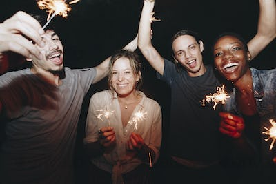 Friends having fun with sparklers in the night