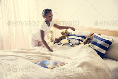 Young teen girl making the bedroom