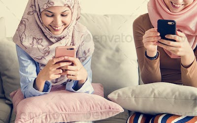 Group of islamic girls sitting on the couch and using smart phones