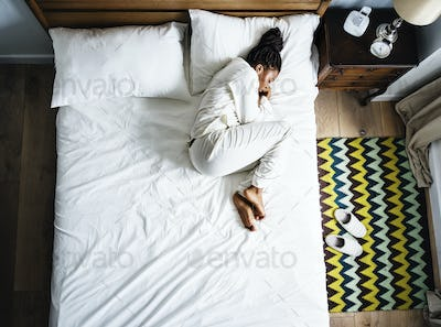 Lonely African American woman on bed sleeping alone