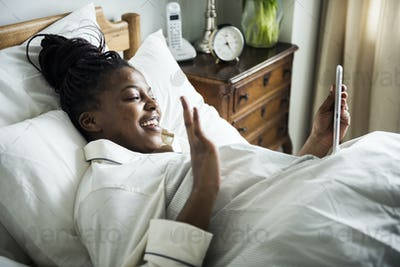 A woman during a video call in bed