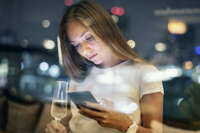 Serious young woman using a smartphone at a rooftop bar in the e