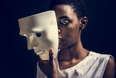 Black woman holding white mask