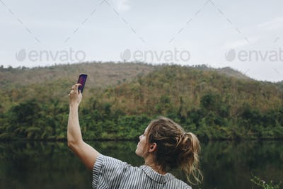 Woman alone in nature raising smartphone above signal problem and smartphone addiction concept