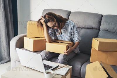 Stressed and frustrated asian business woman holding head in hands