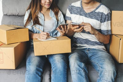 Young asian couple working online business by using smart phone
