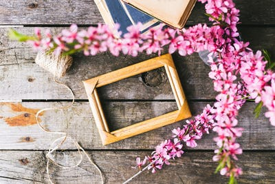 Spring flowers frame and book on a old wooden background