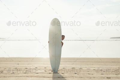 sun-tanned happy brunette (girl, woman, tourist) standing behing surfboard